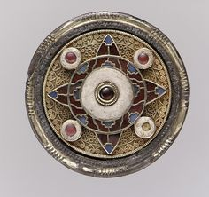 Disk Brooch Date: early 7th century Geography: Made in Faversham, England Culture: Anglo-Saxon Medium: Gold with garnets, glass, and niello Dimensions: Overall: 1 7/8 x 7/16 x 1/16 in. (4.7 x 1.1 x 0.2 cm) Classification: Metalwork-Gold