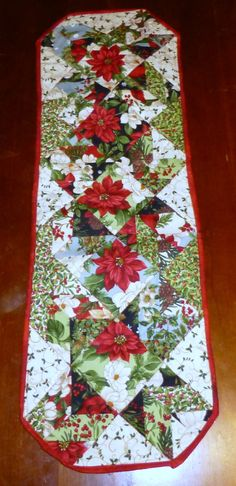 "This Quilted tablerunner features beautiful Pointsettias down the center. It measures 11"" X 34"" and will add some nice color to your room."