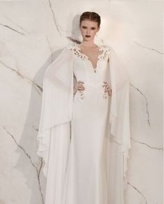 A touch of the past graces this lovely chiffon, mermaid style gown. The sleeves are done in an old fashioned long bat-wing style giving the illusion of a caped gown. The gown itself has beautiful, pea
