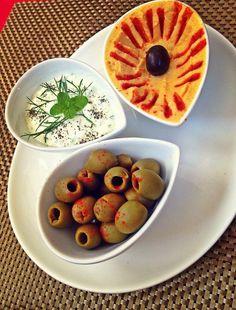 Mezze of marinated chili garlic olives , Tatziki and hummus .