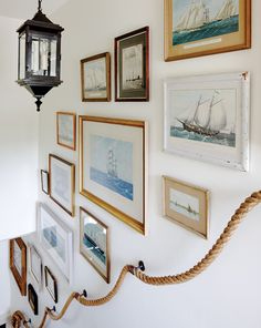 Nautical oil paintings + rope railing.