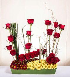 Arreglo de rosas rojas con unas hermosas margaritas enmarcando la base con follaje.