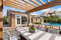 Cottage Patio with exterior stone floors, exterior tile floors, Skylight, Trellis, Custom Attached Wood Pergola