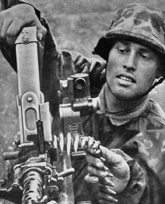 German soldier loading his MG 34 with help from his ammo feed assistant.