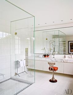 A bright master bathroom featuring a European-style shower and white cabinetry | archdigest.com