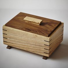 Grain-wrapped ash and walnut keepsake box with splined-miter joints, inset lid, and arched feet.