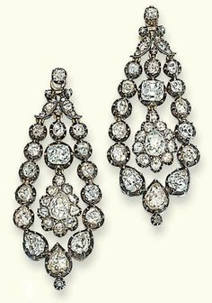 A PAIR OF GEORGE III DIAMOND EAR PENDANTS. Each suspending a pear-shaped drop within an articulated collet surround and foliate surmount set with rose and old-cut diamonds, mounted in silver and gold, some with closed back settings, later diamond collet fitting, circa 1800, 5.1 cm long