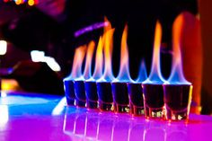 Flaming Blue Jesus  - Flaming Cocktail Drink Recipe    ¼ shot of Rum    ¼ shot of peppermint schnapps    ¼ shot of Peach liqueur    ¼ shot of Tequila    Layer with the rum on top. Light on fire - burn for 5 seconds - blow it out and drink.
