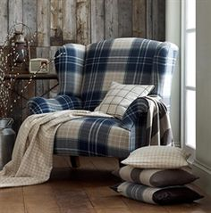 There is something oddly appealing and cozy about a tartan chair (♥ the tiny radio and pussywillows too). I would add a leather ottoman and change the pillows to something softer, maybe floral instead of checks or stripes? Tartan Chair, Furniture, Plaid Couch, Cabin Decor, Chair, Comfy Office Chair, Grey Chair Bedroom, Plaid Chair, Armchair