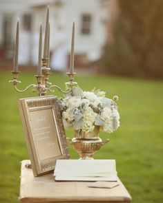 A glamorous, outdoor guest book station, complete with an antique silver candelabra and a flower-filled urn