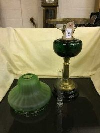 A Victorian green glass oil lamp with chimney and shade