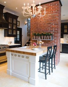 brick wall, the pretty chandelier and this amazing island with bar stools.