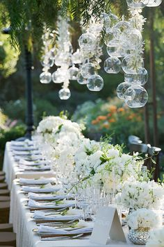 Gorgeous glass bubbles hang over a long banquet table for a fresh, outdoor spring wedding celebration.