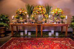Na mesa de doces podem ser montados arranjos altos e baixos, com flores coloridas em estilo tropical, como boca-de-leão, alstroeméria, tango, mini rosa, gérbera, girassol e orquídea. A produção é da Villa Bisutti