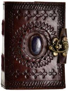 """Hand tooled blank leather journal with an embossed God's Eye & embedded stone. Border embossing may vary. Sizes vary slightly. Leather, handmade paper. 220 pages, latch closure. 3 1/2"""" x 5"""""""