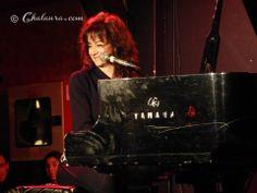 Primer plano de Carmen París mientras toca el piano y luciendo una estupenda sonrisa hacía su público