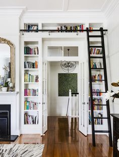 Built-in white bookcase/shelves around doorway, French doors, black ladder on rail, polished timber floorboards, large gilded mirror above marble-top fireplace, white wooden wall panelling (vertical), chandelier in black wire orb, coffered ceiling