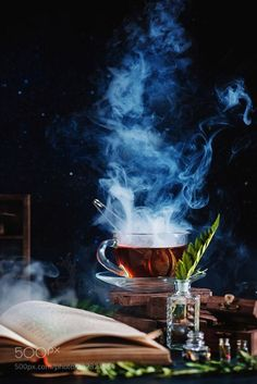 Stock Photo - A cup of tea with a dense steam, an open book, glass bottles and herbs on a dark background Coffee Photography, Food Photography, Images Harry Potter, Tea And Books, Tea Art, Jimin Jungkook, Dark Backgrounds, High Tea, Afternoon Tea