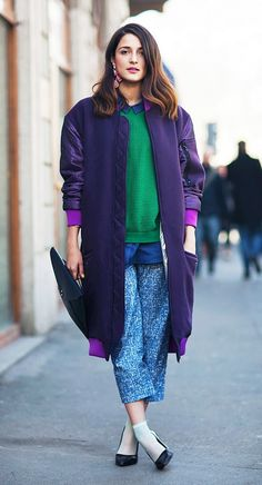 A long bomber jacket is worn over a green sweater with a blue button down, printed cropped pants, a black clutch, socks, and black pumps