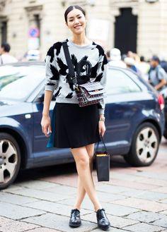 Graphic sweatshirt, black miniskirt, and black oxfords