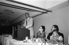 Tom Bradley (L) on a podium at an event. Sylvia and David Cunningham Jr. sit to the right with a child. Photo by Guy Crowder.