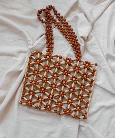 Shoulder bag composed of hand-sewn wooden beads Wood Natural wood varnish Handmade in Istanbul. Each wood beaded bag is formed individually by hand and will therefore have its own individual character, shape and imperfections. Beaded Clutch, Beaded Purses, Beaded Bags, Lv Bags, Purses And Bags, How To Varnish Wood, Spring Bags, Knitted Bags, Handmade Bags