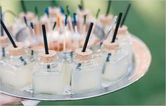 Serve signature drinks—like these margaritas—in mini glass jars with a cork. Drill holes in the cork at an angle and add pretty straws to make for easy sipping.