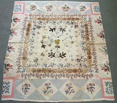 English patchwork with appliqué center and broderie perse blocks.