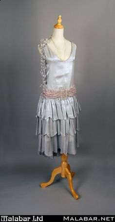 "1920s day silver dress with multilayered skirt, waist sash diamond buckle detail, and shoulder flower cascade. Small pearl necklace to complete the look. (Originally from the production of ""Desert Song"") #1920s #flapper #malabar #costume #costumes #grey #silver #1920sfashion"