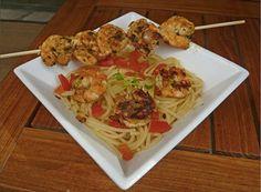 Eplucher les crevettes et les mettre dans un saladier ou une assiette creuse.  Emincer une échalote et parsemer les crevettes.  Ajouter l'huile d'olive, sel, poivre, curry, persil, jus de citron, mélanger et mettre au frais 10 minutes.  Pendant ce temps, faire bouillir un grand volume d'eau salée et faire cuire les pâtes.   Couper les tomates en dés.  Reprendre le mélange avec les crevettes et faire sauter dans une poèle sur feu vif.