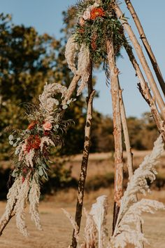 Rustic tepee for wedding ceremony backdrop with pampas grass and mixed fall flowers