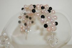 Santuzza Bracelet - ML110B  Beautiful, romantic bracelet inspired by Santuzza, a character in the opera Cavelleria Rusticana.  Features 5 connected strands of natural pink and lilac pearls, as well as shiny cut black onyx stones and matte black onyx stones. Crocheted with metallic silver thread. Silver-plated heart lock.  Please note that this item is MADE TO ORDER. Melissa will make a similar one for you. No two handmade items will turn out exactly the same.  $110.00