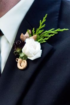 A simple white rose gets a pop of visual interest from a cluster of acorns and a raffia-wrapped stem.