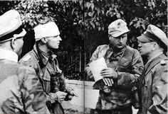 The wounded commander of Panzer Regiment 12, Max Wünsche, with head bandage listens to his Divisional Commander Kurt Meyer while commander of the 26th Panzer-Grenadier, Bernhard Krause, looks on. They are all part of 12th SS-Panzer Division Hitlerjugend...