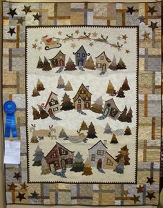 """Here Comes Santa Claus"", 50 x 65"", by Diana K. Trost. The houses and Santa patterns are from ""Welcome to the North Pole"" by Piece o' Cake Designs. Photo by Fabric Therapy: 2015 Sauder Village Quilt Show."
