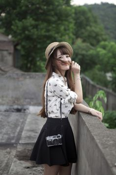 White printed button top with a black skirt and tights and a black shoulder purse and a hat