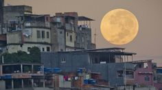 """A """"supermoon"""" sets behind the Mare shanty town complex in Rio de Janeiro, Sunday, May 6, 2012. A supermoon is the coincidence of a full moon (or a new moon) with the closest approach the moon makes to the Earth. (AP Photo/Victor R. Caivano)"""