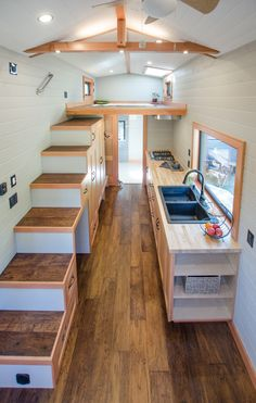 The kitchen includes hand-built birch cabinetry with soft-close drawers and cupboards, two large pantries under the storage stairs, a gas cooktop, and an apartment size refrigerator. A black granite sink sits in front of a large picture window. Tiny House Plans, Tiny House On Wheels, Ideas Cabaña, Apartment Size Refrigerator, Tiny Houses For Sale, Mini Houses, Small Houses, Tiny House Movement, Tiny Spaces