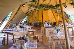 A tipi decorated with hops and very simple purple wedding decor. It feels very French and relaxed