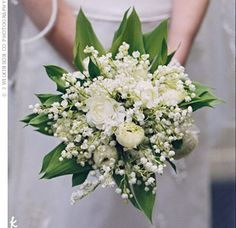 Amelita carried the wedding's signature flower, lily of the valley, and white ranunculus down the aisle.