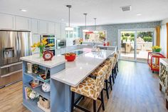 Bold red and yellow accessories add vivid color to this contemporary eat-in kitchen. A spacious island has room for four and also features a built-in bookshelf to store cookbooks and kitchen accessories.