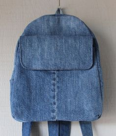 This is a handmade backpack made from upcycled jeans and lined with a pink, blue and white floral patterned cotton fabric and accented with a two interior pockets. The outside has a large front velcro pocket, two side pockets and a zipper closure with a top loop for hanging. This handbag is lined with interfacing throughout the bag for sturdiness. Dimensions: 10 (W) x 12 1/2 (H) x 3 1/2 (D) Straps are 27 each Please feel free to contact me for custom orders. Thank you.