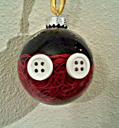 DIY String Mickey Ornament Need: Red and Black String, Buttons, Hot Glue(Gun), Clear Glass Ornament(available at any craft store) What to do: Fill ornament half full with red string, then up to the top with black. Hot glue buttons down. Voila! Easy and fun for kids to do
