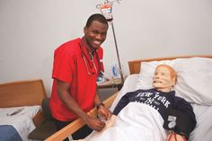 Caldwell College Nursing student simulates an examination on the Laerdal SimMan 3G manikin.