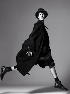 black and white fashion photography of walking woman dressed in a black coat in combination with a hat and high flat leather shoes | Fashion + Photography | Stella Tennant for Vogue | inspiration |