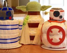 Choose your Set of 2 Star Wars Diaper Cakes and make the perfect match for the most amazing Star Wars Baby Shower ever! You wont see anything like this anywhere else. Your choice of 2 diaper cakes come with a newborn size crocheted hat, perfect for newborn photo shoots! (Choose your Set of 2 from the drop down menu on the right side)  Made from: Size 1 Pampers Swaddlers Hand Crocheted Princess Leia Hat (0-1 month size) Hand Crocheted Yoda Hat (0-1 month size) Hand Crocheted R2D2 Hat (0-1…
