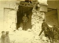 Photograph by W.D. Hogan of an Irish Free State Army soldier standing on guard with his rifle on the breached wall of a large building; the building has sustained extensive damage to its outer stone wall and coping stones; a second soldier is standing at ease to the right of the building; a group of small boys has congregated and is looking on; one boy is smoking.