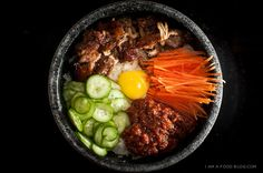 Bibimbop. One of my FAVORITE Korean foods! (Add spicy red pepper sauce and mix. The pot is very hot and it cooks the egg as everything is mixed together!)