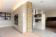 A SieMatic kitchen by Stuart Frazer in the UK, with onWall system accessories, featuring a Norstone natural stone wall