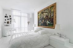 This modern bedroom also has an eye-catching contrast element. Here everything is white except for the artwork. The white ceiling, walls, floor and furniture create a neutral and bright background for the elegant painting displayed on the wall adjacent to the bed. A small work area is also present and features a few small photos on the wall.